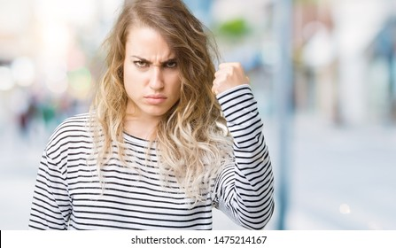 Beautiful young blonde woman wearing stripes sweater over isolated background angry and mad raising fist frustrated and furious while shouting with anger. Rage and aggressive concept.