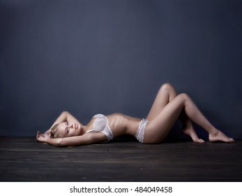 Beautiful young blonde woman wearing white lace lingerie laying on the floor.