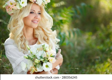 Beautiful young blonde woman in white dress and flower wreath with swing in summer outdoors. Woman outdoor. Summer portrait. Blonde girl in flowers.
