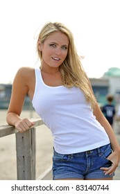 Beautiful young blonde woman in white tank top and denim shorts leaning on a railing at a beach boardwalk - smiling