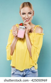 Beautiful young blonde woman in yellow top drinking strawberry smoothie with a straw in a summer day. Healthy organic drinks concept. People on a diet.