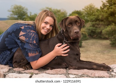 A beautiful young blond-haired woman with her big brown labrador dog