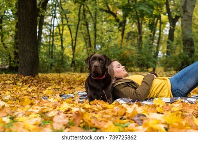 A beautiful young blond-haired woman is laying with her big brown labrador dog in the park, in a pile of autumnal fallen leaves