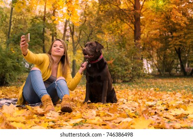 A beautiful young blond-haired woman is taking a selfie with her big brown labrador dog in the park, in a pile of autumnal fallen leaves