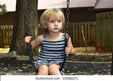 A beautiful young blue eyed preschool girl on a swing, looking candidly out  from swing staring, not smiling.