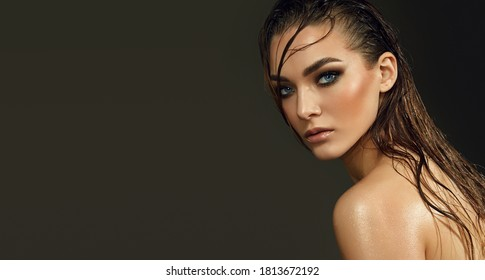 Beautiful young blue-eyed woman with wet skin and wet hair in the studio on a gray background. Close-up portrait.