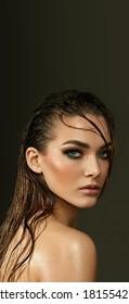 Schöne junge blauäugige Frau mit nasser Haut und nassem Haar im Studio auf grauem Hintergrund. Nahaufnahme-Portrait.