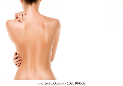 beautiful young body. Naked back of a woman, isolated on white background. Skincare treatment concept. Beautiful female body at studio. Body care, self-massage, pain concepts. Young caucasian model
