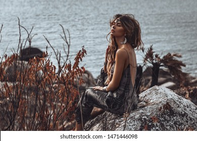 beautiful young boho style woman sitting on stone at sea background