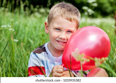 Beautiful young boy with balloon in his hands outdoors in park