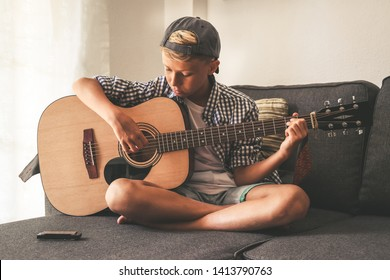 Beautiful young boy playing acoustic guitar. Music student exercises alone at home. Trendy caucasian child plays instruments sitting legs crossed on the sofa. Blonde guy enjoying melody of a song