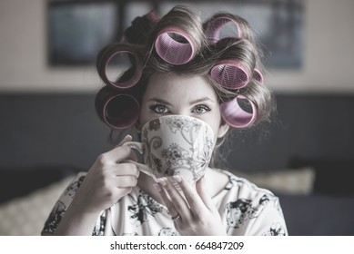 Beautiful young bride to be getting ready for her wedding with coffee and curlers.