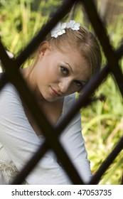 Beautiful, young bride behind bars. Metaphor.