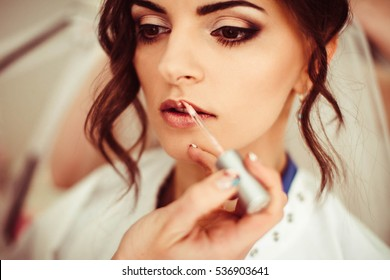 beautiful and young bride doing makeup in the morning