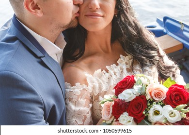 beautiful young bride and groom on the boat. the bride is holding a bouquet, the bridegroom is hugging her. they are happy and love each other. summer, day, park
