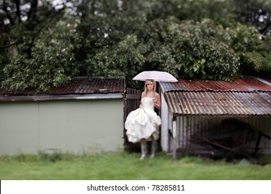 Beautiful young bride in her wedding dress, stands in the rain with colorful Umbrella