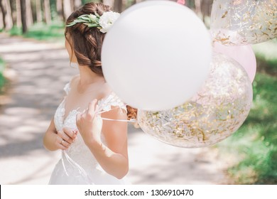 Beautiful young bride holding several air balloons in hands while standing outside on sunny warm day. Horizontal color photography.