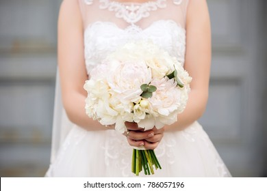 Beautiful young bride holds wedding bouquet of pastel beige tones peonies in hands with french manicure on blured background. Closeup view