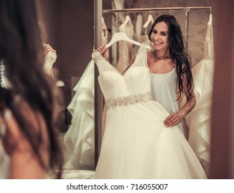 Beautiful young bride is looking into the mirror and smiling while choosing elegant wedding dresses in modern wedding salon