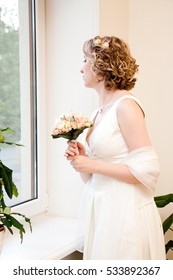 Beautiful young bride looking from the window