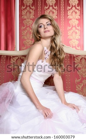 51d93d386591 Beautiful young bride in luxurious red interior, sitting on the sofa,  wearing white dress decorated with pink jewels - Image