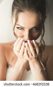 Beautiful young bride with makeup and hairstyle in bedroom, newlywed woman final preparation for wedding. Happy girl waiting groom. Portrait soft focus