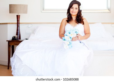 beautiful young bride sitting on bed with bouquet