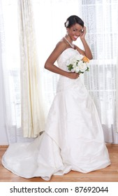 Beautiful Young Bride Standing by Window Smiling
