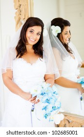 beautiful young bride standing next to mirror