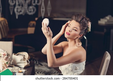 Beautiful young bride wearing fashion gown sitting on chair and looking into hand mirror