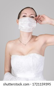 Beautiful young bride in a wedding dress and a white medical mask on her face. Wedding Style spring-summer 2020