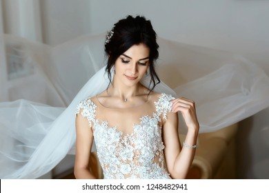 Beautiful young bride with wedding makeup and hairstyle in bedroom. Beautiful bride portrait with veil. Closeup portrait of young gorgeous bride. Wedding.