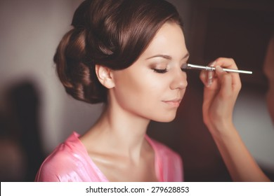 Beautiful young bride with wedding makeup and hairstyle in bedroom, newlywed woman final preparation for wedding. Happy Bride waiting groom. Marriage Wedding day moment. Bride portrait soft focus
