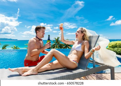 Beautiful young bride in a white bikini, veil and garter on her leg sitting with groom enjoying glass of champagne on the edge of the infinity-edge pool. Tropical sea in the background.