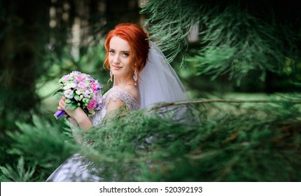 beautiful and young bride in white dress standing outdoors