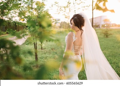 beautiful and young bride in white dress walking in the garden