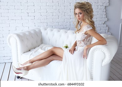 Beautiful young bride in white dress. Blond hair, makeup, posing indoor.
