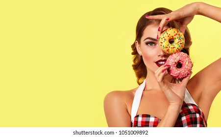 Beautiful young bright girl in retro style holds two bright donut in hands.