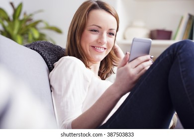 Beautiful young brown haired girl taking a rest on a sofa while playing with her smartphone