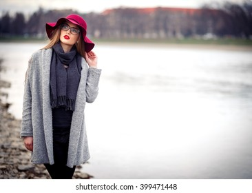 beautiful young brown-haired woman with long hair, makeup with bright red lips, wearing a gray coat, black pants, a scarf, a hat and sunglasses walking near the river