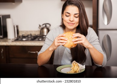 Beautiful young brunette about to bite a delicious hamburger at home