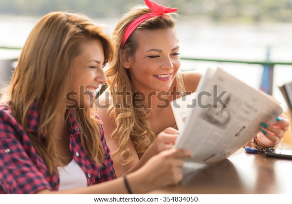 Beautiful young brunette and blond girl sitting in a cafe, drinking coffee and reading newspapers