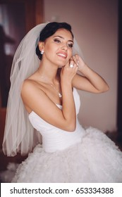 Beautiful young brunette bride is getting ready in the morning. Wedding day preparations. Bride is posing in a wedding dress. Waiting for a groom