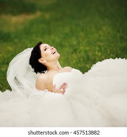 Beautiful young brunette bride wearing white dress laying on grass in garden