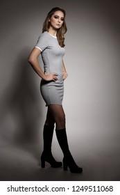 Beautiful young brunette caucasian woman in gray dress