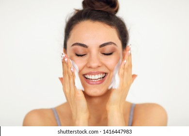 Beautiful young brunette caucasian woman washing her face with foam