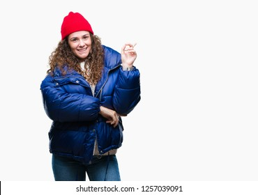 Beautiful young brunette curly hair girl wearing winter coat, wool cap and sweater over isolated background with a big smile on face, pointing with hand and finger to the side looking at the camera.