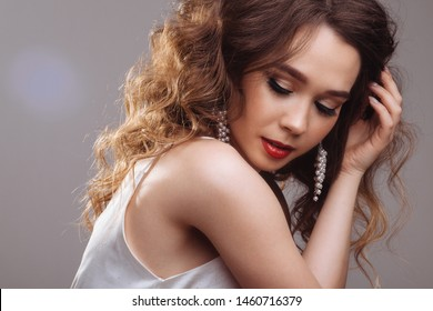 Beautiful young brunette with curly long hair and red lips on a monochrome gray background. Portrait of an attractive girl with a Hollywood makeup, red lips, sumptuous curls. The girl smiles beautiful