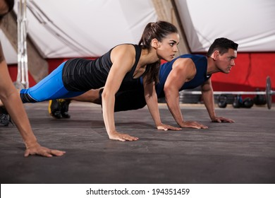 Beautiful young brunette doing some push ups with some other people at a gym