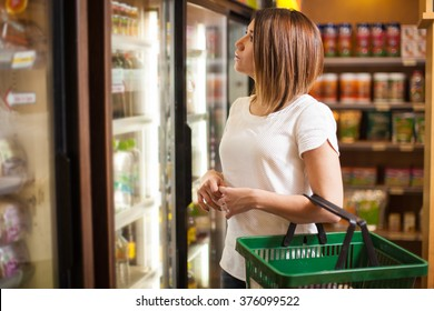 Beautiful young brunette doing some shopping at a supermarket and looking at a refrigerator